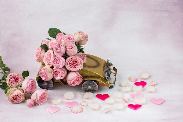 Hartjes van satijn, rozenblaadjes en een boeket roze rozen in de auto
