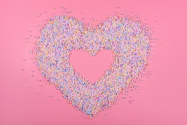 Hartkader gemaakt van pastelkleurige ballen op roze piepschuim of piepschuim
