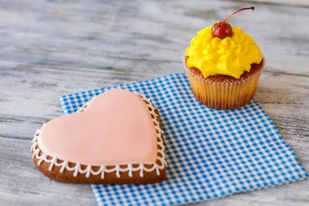 Hartkoekje en geel cupcakegebak op geruite servetverrassing voor degenen van wie je houdt, zoek een gelegenheid...
