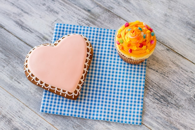 Hartkoekje en oranje cupcake-snoepgoed op servet, zoete lekkernijen en goede gevoelens feliciteren ...