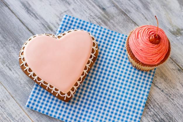 Hartkoekje en roze cupcakegebak op blauw geruit servet kleine vakantie voor geliefden vinden vreugde ...