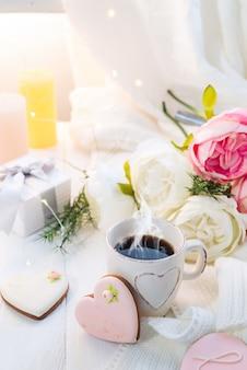 Hartkoekjes met kop van koffie op houten achtergrond met plaid