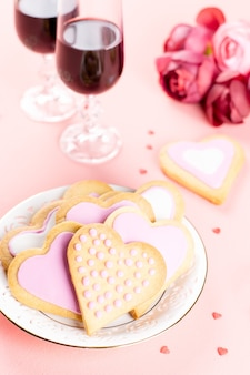 Hartkoekjes, wijnglazen en wijn op pastelroze