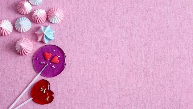 Hartlollies en marshmallows op roze achtergrond