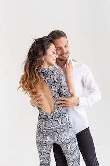 Hartstochtelijk paar dat een latijnse dans op witte muur danst