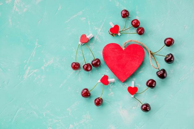 Hartsymbool met rode rijpe geïsoleerde kersen. concept van het leven. stijl van een gezonde levensstijl. bescherming van leven en gezondheid. liefdesymbool of romantiek van valentijnsdag concept. 14 februari kalender.