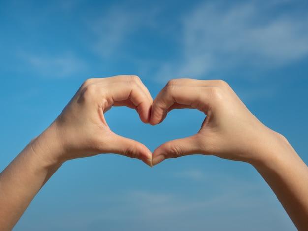 Hartsymbool uit handen op de blauwe hemel.