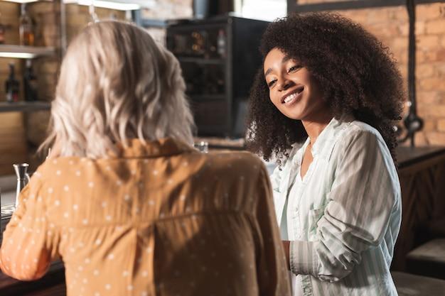Hartverwarmend gesprek. mooie gekrulde vrouw zit naast haar beste vriend aan de bar en praat met haar terwijl ze liefdevol glimlacht