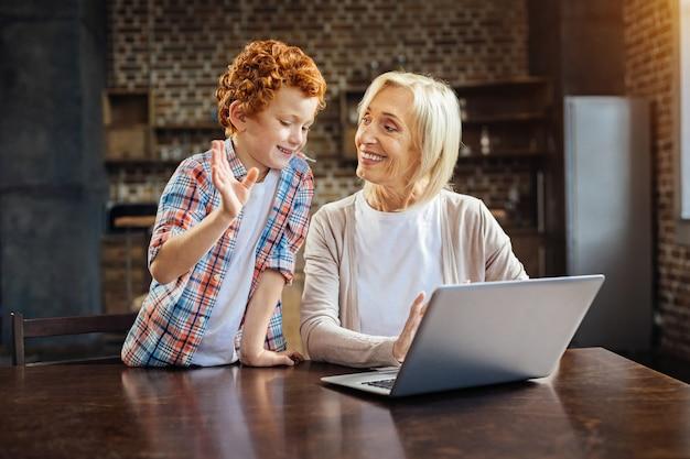 Hartverwarmende verhalen. emotionele roodharige jongen gebaart terwijl hij een aangenaam gesprek heeft met zijn glimlachende oma die thuis op laptop werkt.
