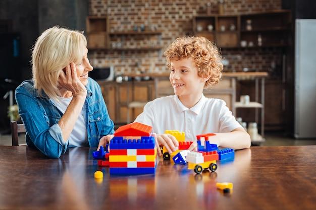 Hartverwarmende verhalen. liefdevolle oma die haar hoofd op een hand laat rusten terwijl ze met een brede glimlach naar haar kleinkind kijkt terwijl ze met een bouwdoos speelt.