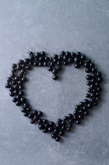 Hartvorm gemaakt met zwarte bessen op een grijze achtergrond. bovenaanzicht