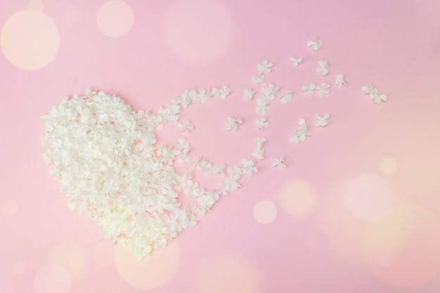 Hartvorm gemaakt van bloemen op witte achtergrond. plat lag. valentines, liefde en bruiloft concept ideeën.
