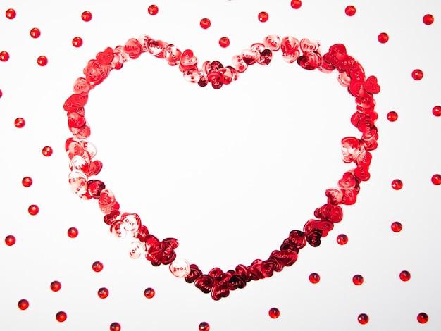 Hartvorm gemaakt van hartvoorwerpen en rode kristallen op witte achtergrond met kopie ruimte, gelukkige valentijnsdag, moederdag, plat leggen, bovenaanzicht