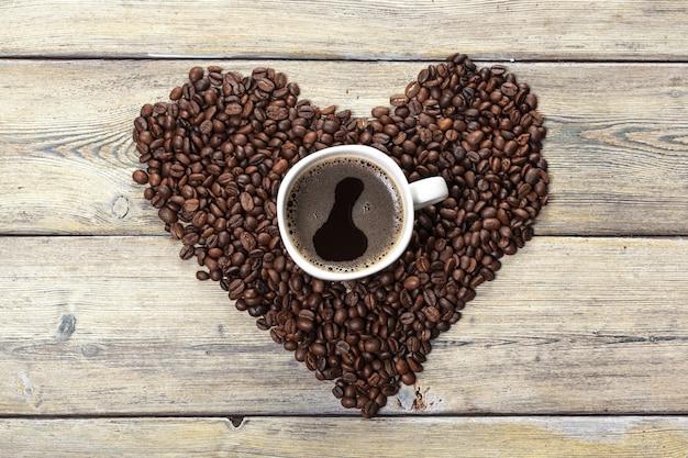 Hartvorm gemaakt van koffiebonen op houten oppervlak.