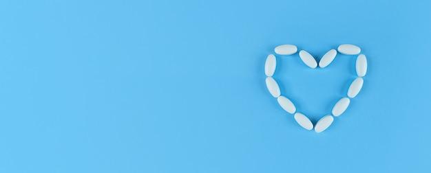 Hartvorm gemaakt van witte tabletten op een blauwe tafel met kopie ruimte.