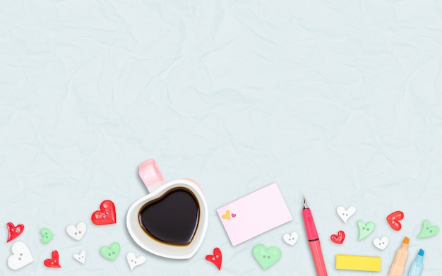 Hartvorm koffiekopje met kleur liefdesymbool op lichtblauwe kleur gerecycled papier achtergrond, plat ontwerp, uitzicht vanaf de top.