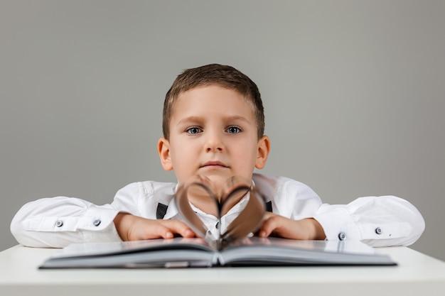 Hartvorm papieren boek en schattig kind jongen op grijze achtergrond. valentijnsdag.