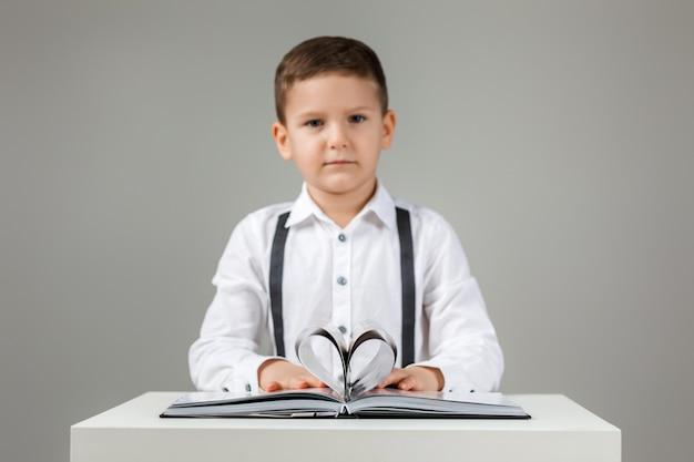 Hartvorm papieren boek en schattig kind jongen op grijze achtergrond