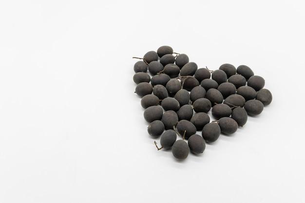 Hartvorm van gedroogd zwart dialium met shell die op witte ruimte wordt geïsoleerd.