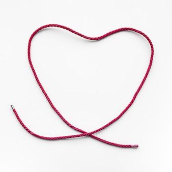 Hartvorm van rood garen, touw op blauwe achtergrond.