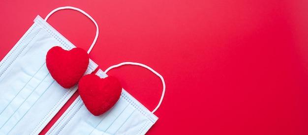Hartvormdecoratie en medisch gezichtsmasker op rode achtergrond tegen besmetting met de ziekte van coronavirus