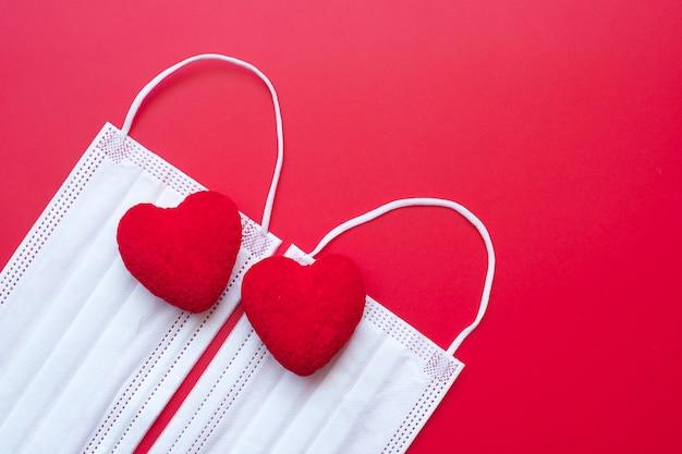Hartvormdecoratie en medisch gezichtsmasker op rode achtergrond tegen besmetting met de ziekte van coronavirus.