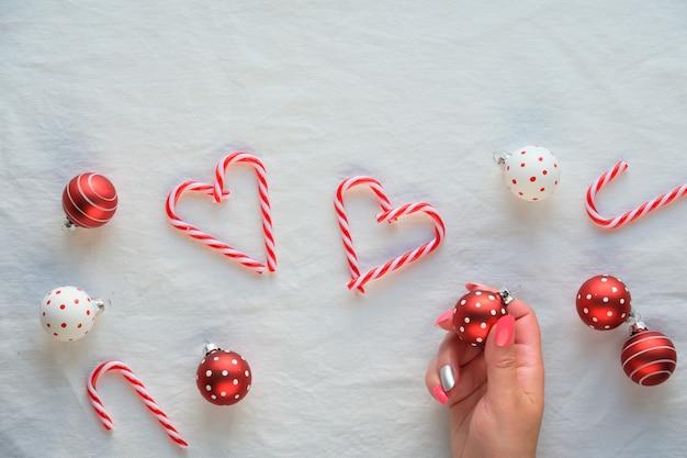 Hartvormen gemaakt van zuurstokken, rode en witte snuisterijen met stippen op wit textiel. hand vasthouden