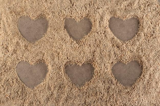 Hartvormen op een achtergrond van zaagsel wordt gemaakt dat