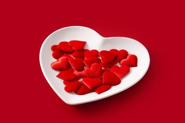 Hartvormig bord met rode harten erin op rood
