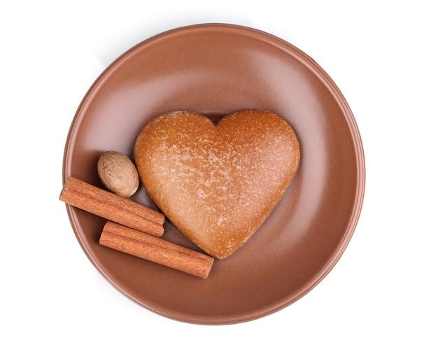 Hartvormig koekje met kaneel en nootmuskaat op schotel op wit