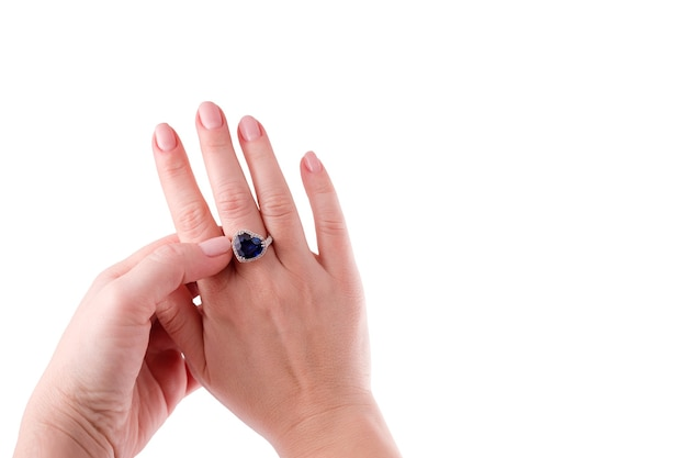 Hartvormige blauwe saffier kostbare ring aan de hand van de vrouw geïsoleerd op een witte achtergrond