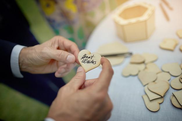 Hartvormige bord met de woorden beste wensen in de handen van een man