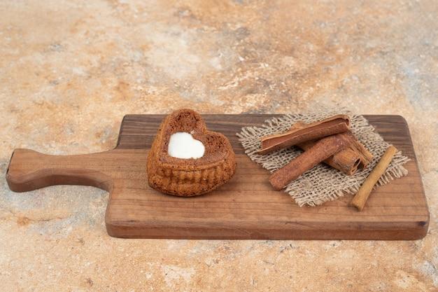 Hartvormige cake en kaneelstokjes op een houten bord.