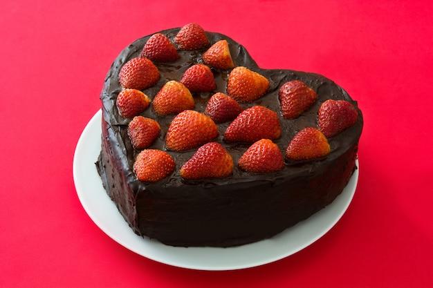 Hartvormige cake voor valentijnsdag of moederdag geïsoleerd op rode achtergrond