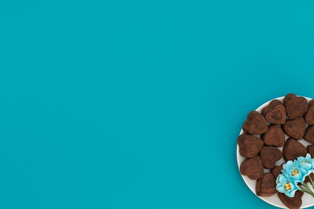Hartvormige chocolaatjes in witte schaal met blauwe bloemen