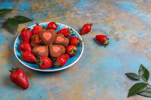 Hartvormige chocolade en aardbei koekjes met verse aardbeien, bovenaanzicht