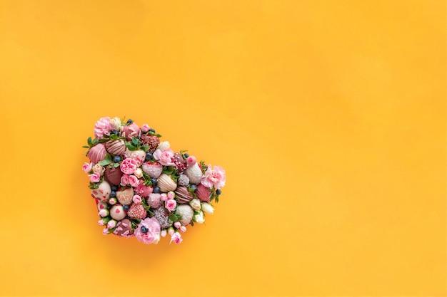 Hartvormige doos met handgemaakte aardbei in chocolade en bloemen als een geschenk op valentijnsdag op oranje achtergrond met vrije ruimte voor tekst