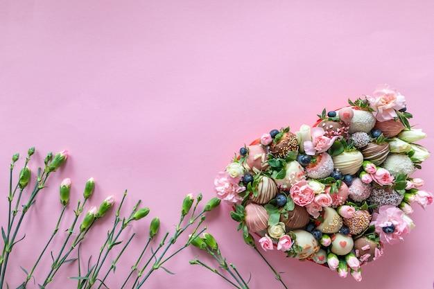Hartvormige doos met handgemaakte chocolade bedekte aardbeien met verschillende toppings en bloemen als een geschenk op valentijnsdag op roze achtergrond met vrije ruimte voor tekst