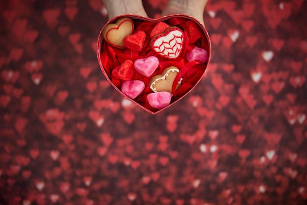 Hartvormige doos, met hartvormige jelly beans, hartvormige koekjes en rode achtergrond