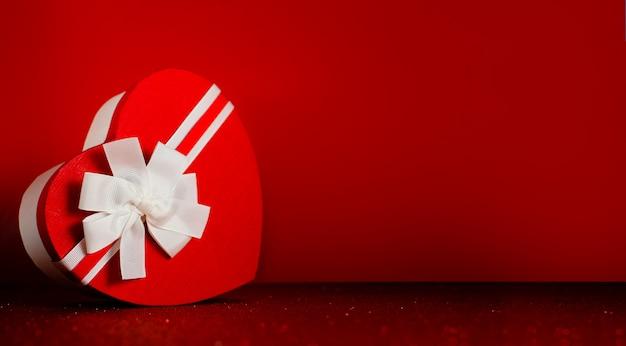 Hartvormige doos met lint rode glinsterende achtergrond. sint valentijnsdag en verlovingsconcept.
