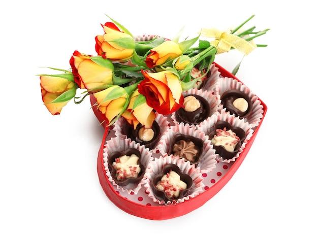 Hartvormige doos met snoepjes en bloemen, geïsoleerd op wit