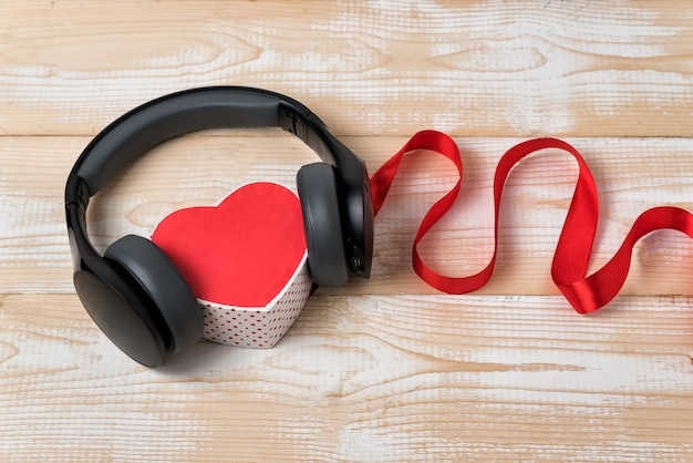 Hartvormige doos met stereo hoofdtelefoon en rood lint. muziek van het hart-concept. houten achtergrond
