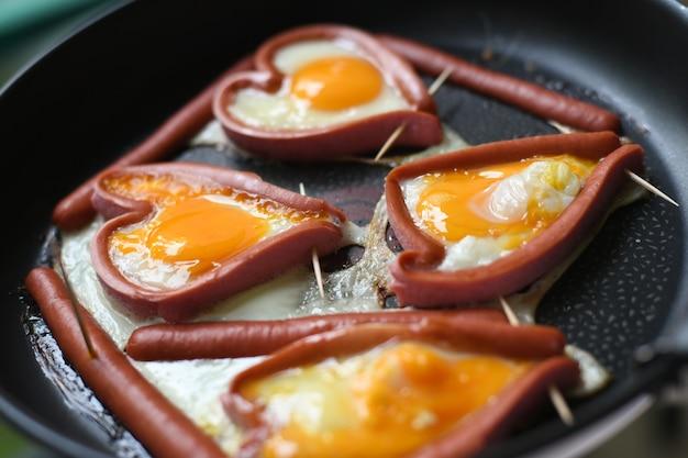 Hartvormige gebakken eieren in worstjes in een koekenpan