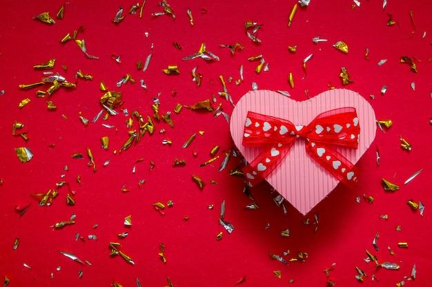 Hartvormige geschenkdoos op rode achtergrond met feestelijke glitterdeeltjes