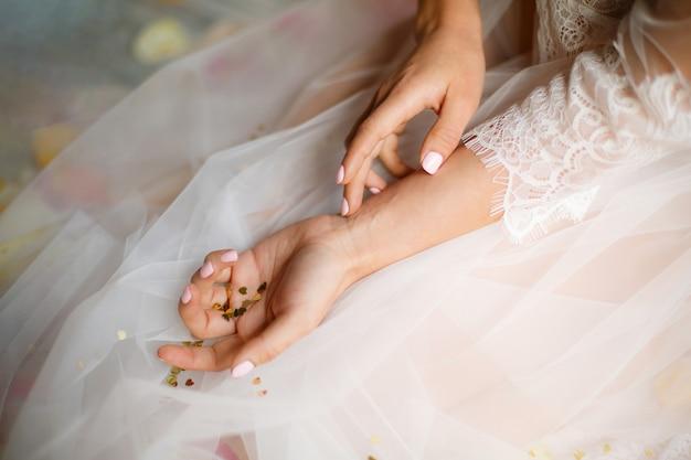 Hartvormige gouden confetti liggen op handen, mooie vrouwelijke handen