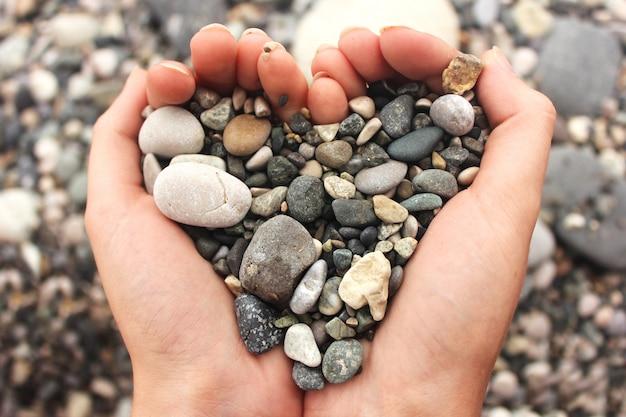 Hartvormige kleine steentjes in vrouwelijke handen