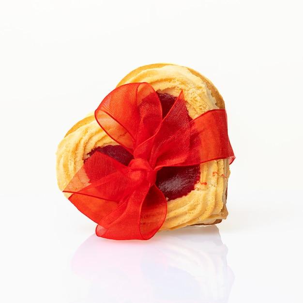 Hartvormige koekjes gebonden met een rode strik op een witte achtergrond. valentijnsdag of verjaardag concept.