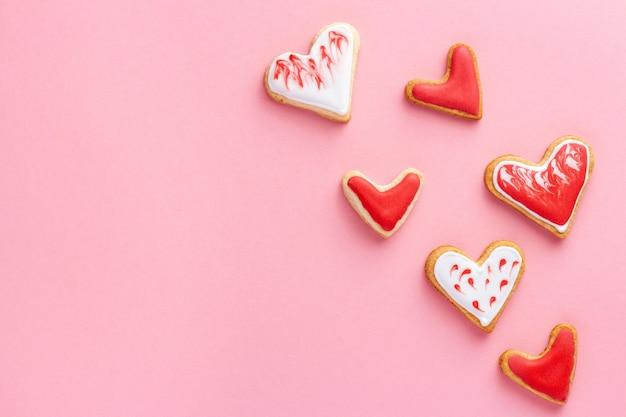Hartvormige koekjes geglazuurd met suikerglazuur voor valentijnsdag op roze achtergrond