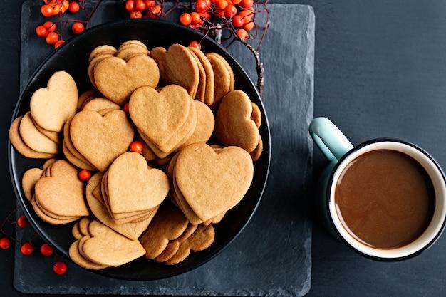 Hartvormige koekjes met asbessen en een mok cacao op een tafel