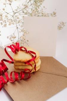 Hartvormige koekjes met een rood lint en een wit boeket bloemen.